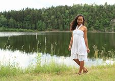 Pretty girl walking by water. Pretty Papuan girl in white dress - young Indonesian woman waling and posing by water of Dam Rimov in Czech Republic Stock Photos