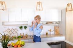 Pretty girl walks into kitchen and stretches, enjoying morning c Stock Photos