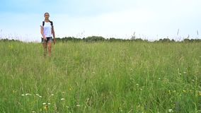 Pretty girl wanders with funny dog along green meadow. Pretty girl wanders with funny dog on green meadow with flowers against forest on horizon under blue sky stock video