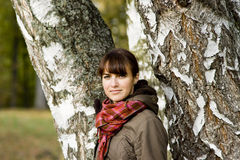 Pretty girl in warm coat near birches Stock Images