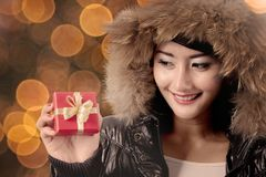 Pretty girl with warm jacket and Christmas gift. Pretty girl wearing a warm jacket while showing a Christmas gift with sparkle light in the background Royalty Free Stock Photo