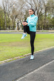 Pretty girl warming up in the stadium. Girl with a sports body is doing exercises outdoors in spring Royalty Free Stock Images