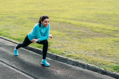 Pretty girl warming up in the stadium. Girl with a sports body is doing exercises outdoors in spring Stock Image