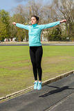 Pretty girl warming up in the stadium. Girl with a sports body is doing exercises outdoors in spring Stock Images