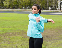 Pretty girl warming up in the stadium. Girl with a sports body is doing exercises outdoors in spring Royalty Free Stock Photography