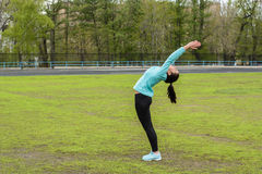 Pretty girl warming up in the stadium. Girl with a sports body is doing exercises outdoors in spring Stock Photo