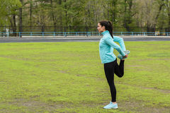 Pretty girl warming up in the stadium. Woman with sporty body doing exercises outdoors in spring Royalty Free Stock Photography