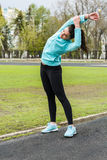 Pretty girl warming up in the stadium. Woman with sporty body doing exercises outdoors in spring Stock Images