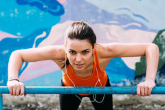 Pretty girl warming up in the stadium. Woman with sporty body doing exercises outdoors in spring Royalty Free Stock Photo