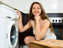 Pretty girl washing clothes in washer Royalty Free Stock Photography