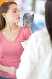 Pretty girl watching her sick parrot in vet clinic Stock Image