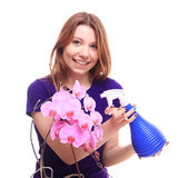 Pretty girl watering orchid flower with spray Royalty Free Stock Photos
