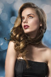 Pretty girl with wavy hair on shoulder looks up. Beautiful woman with long wavy hair and dark dress, her face is turned at right and she looks up Royalty Free Stock Photos