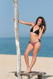 Pretty girl wear bikini, standing on a wooden stand on the sand Stock Photos