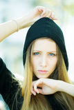Pretty girl wearing hood. Portrait closeup of pretty blond girl with straight long hair flowed over her breast wearing black hood hands around face posing on Royalty Free Stock Photo