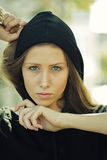 Pretty girl wearing hood. Portrait closeup of pretty blond girl with straight long hair flowed over her breast wearing black hood hands around face posing on Royalty Free Stock Photos