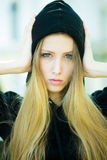 Pretty girl wearing hood. Portrait closeup of pretty blond girl with straight long hair flowed over her breast wearing black hood pin hands to head posing on Royalty Free Stock Photo