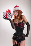 Pretty girl wearing pinup outfit and Santa Claus hat, holding gi Royalty Free Stock Photo