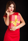 Pretty girl is wearing red fashion dress with gift Royalty Free Stock Photo