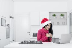 Pretty girl with laptop and Santa hat Stock Image