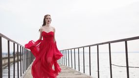 Fashion young woman in long gown is fleeing over old ferry dock, front view stock footage