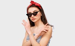 Pretty girl wearing summer striped blouse, black trendy sunglasses and red headband, making rejection gesture. Beautiful young brunette woman making stop gesture stock photos
