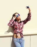 Pretty girl wearing a sunglasses and checkered shirt makes self-portrait on the smartphone outdoors Stock Photos