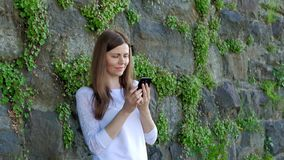 Pretty girl in a white blouse using smartphone. Vintage wall of wild stone in the background stock video