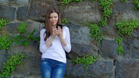 Pretty girl in a white blouse using smartphone. Vintage wall of wild stone in the background. stock video footage