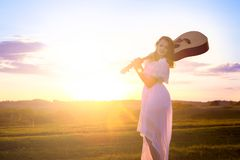 Pretty girl in white dress with acoustic guitar standing in the field. Sunset evening sky stock images