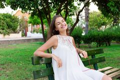 A pretty girl in a white dress is listening to her favourite song on the bench in the park. She enjoys and is having fun.  stock image