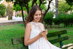 A pretty girl in a white dress is listening to her favourite song on the bench in the park. She enjoys and is having fun.  royalty free stock image
