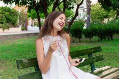 A pretty girl in a white dress is listening to her favourite song on the bench in the park. She enjoys and is having fun.  stock photo
