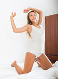 Pretty girl on white sheet smiling in bed Royalty Free Stock Photo