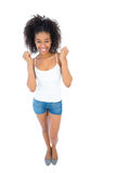 Pretty girl in white top and denim hot pants cheering at camera Stock Images