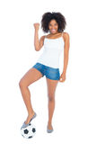 Pretty girl in white top and denim hot pants with football Royalty Free Stock Photography