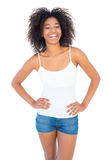 Pretty girl in white top and denim hot pants smiling at camera Royalty Free Stock Photo