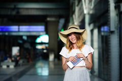 Pretty girl in a wide-brimmed hat with the passport and tickets in a hand. Royalty Free Stock Photo