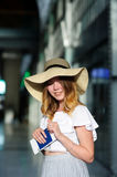 Pretty girl in a wide-brimmed hat with the passport and tickets in a hand. Royalty Free Stock Images