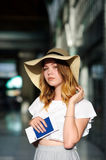 Pretty girl in a wide-brimmed hat with the passport and tickets in a hand. Girl posing. Railway station. Summer holiday royalty free stock photo