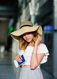 Pretty girl in a wide-brimmed hat with the passport and tickets in a hand. Girl posing. Railway station. Summer holiday stock images