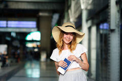 Pretty girl in a wide-brimmed hat with the passport and tickets in a hand. Girl posing. Railway station. Summer holiday royalty free stock image