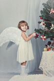 Pretty girl with wings dresses up Christmas tree Royalty Free Stock Image