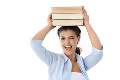 Pretty girl winking with books on her head Royalty Free Stock Photos