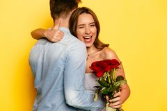 Pretty girl winking and showing a thumb while hugging her boyfriend. Attractive young women with red roses winking and showing a thumb while hugging her Royalty Free Stock Photos