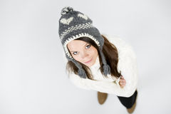 Pretty girl in winter clothes looking up with folded arms. Stock Images