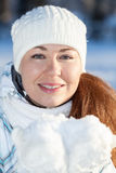 Pretty girl in winter clothing with full guest snow in hands in mittens Royalty Free Stock Photos