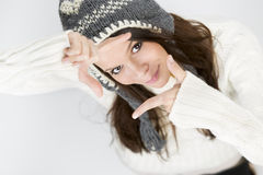 Pretty girl in winter clothing making a photo frame. Stock Photos