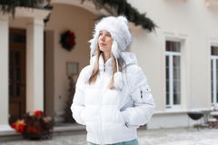 Pretty girl in the winter jacket looking up near the home. Outdoors Royalty Free Stock Image
