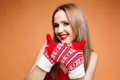 Pretty girl with winter mittens. Studio portrait of lovely brunette girl with bright make-up in winter themed mittens royalty free stock photo